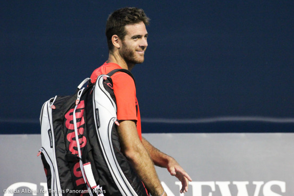 Del Potro smiles with racquet bag