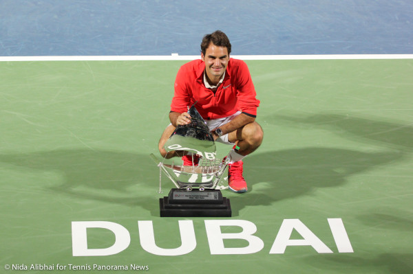 Federer with trophy above Dubai on court